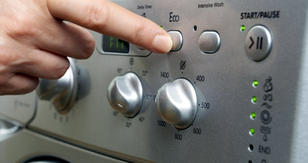 Woman Selecting Economy Program On Washing Machine To Save Energy